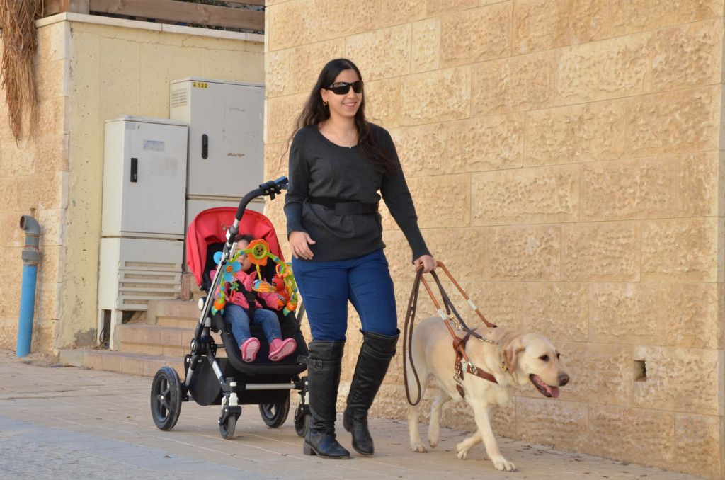 Orit is able to go out with daughter in a pram lead by her dog
