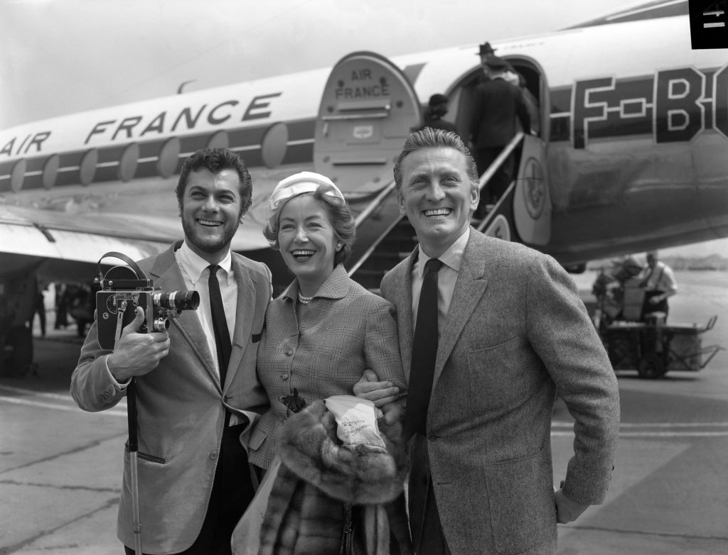 Hollywood film star Kirk Douglas and his wife Anne Buydens being met by Tony Curtis, left, on their arrival at London Airport from Paris. (Photo credit: PA Wire)