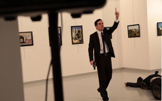 A man identified as Mevlut Mert Altintas stands over Andrei Karlov, the Russian Ambassador to Turkey, after shooting him at a photo gallery in Ankara, Turkey(AP Photo/Burhan Ozbilici)