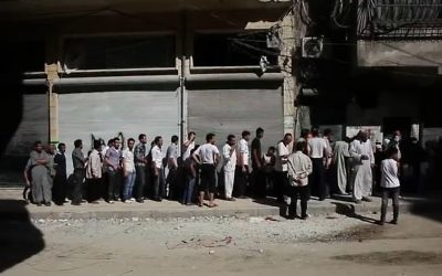 People of Aleppo waiting in a bread line during the civil war