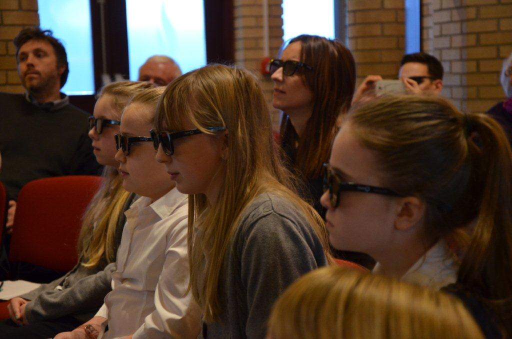 Students with 3D glasses, listening to survivors speak
