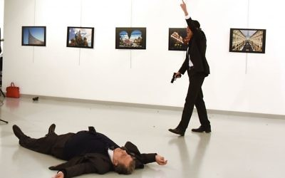 A man identified as Mevlut Mert Altintas stands over Andrei Karlov, the Russian Ambassador to Turkey, after shooting him at a photo gallery in Ankara, Turkey (Press Association)