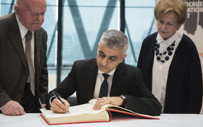 Sadiq Khan signing the Holocaust Educational Trust's  book of commitment, alongside Holocaust survivors Ben Helfgott (left) and Mala Tribich (right)