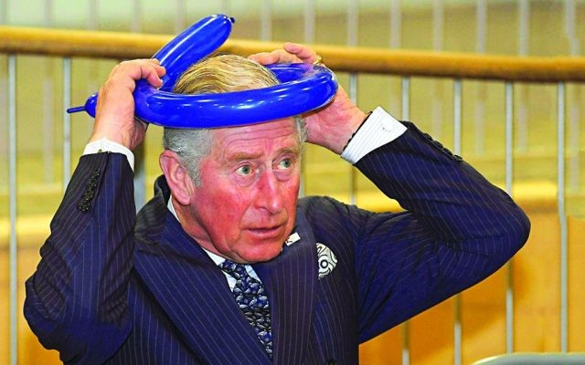 Prince Charles fashioning a balloon crown during his visit to the school