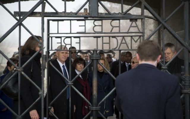 """Mike Pence looks through the camp gates which reads """"Arbeit macht frei"""" - a German phrase meaning """"work sets you free"""""""
