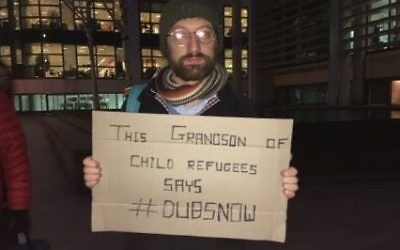 A descendent of a refuge holds a placard urging the government to allow in more children