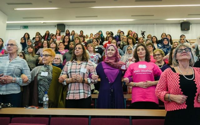 Jewish and Muslim women link arms at the inaugural Nisa-Nashim conference.   (Picture credit: Yakir Zur)