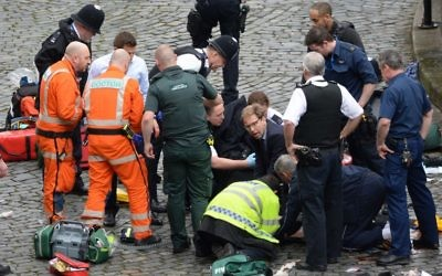 Conservative MP Tobias Ellwood (centre) helps emergency services attend to a police officer outside the Palace of Westminster, London, after a policeman was stabbed and his apparent attacker shot by officers in a major security incident at the Houses of Parliament. (Photo credit: Stefan Rousseau/PA Wire)