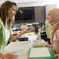 Daniella Pears with a Muslim volunteer cooking a three course meal for the homeless together, on Sadaqa Day