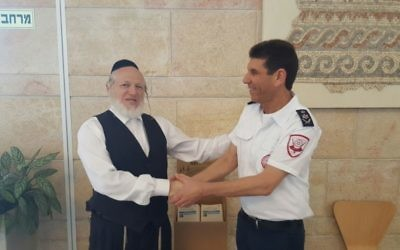 Magen David Adom and ZAKA officials shaking hands as they agree to save more lives together