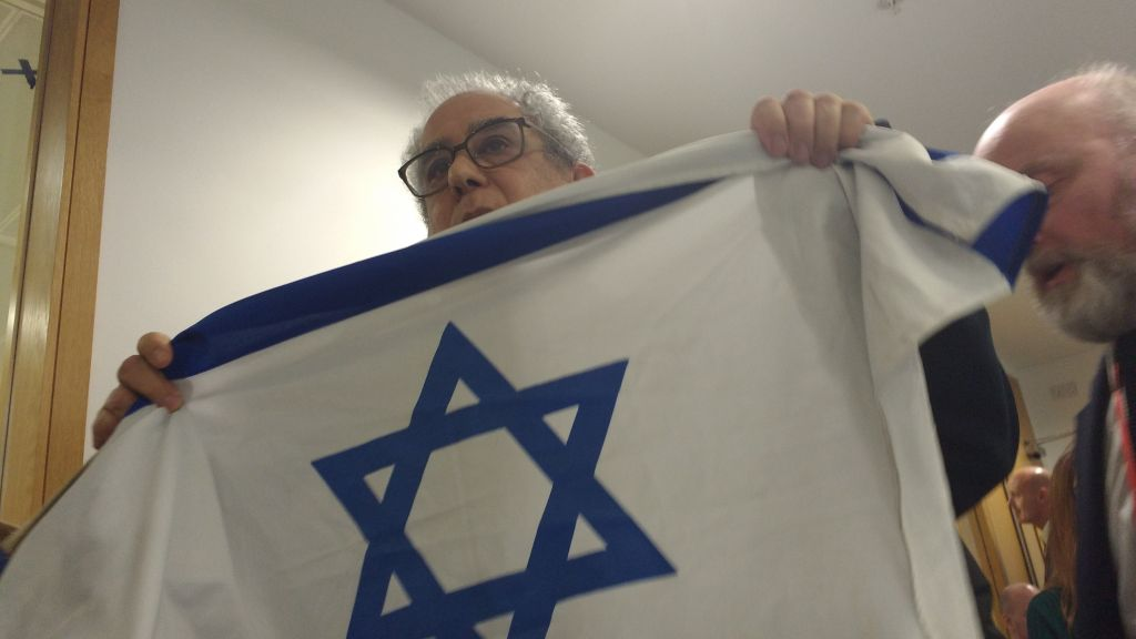 Pro-Israel activist Jonathan Hoffman being led out the room, holding an Israeli flag