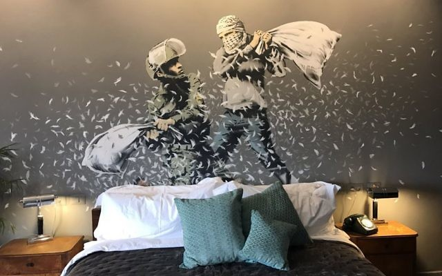 An Israeli solider and Palestinian man have a pillow fight in one of the Banksy artworks on the walls of a hotel he has created in the Palestinian territories. [Picture: Channel 4] (March 2017)