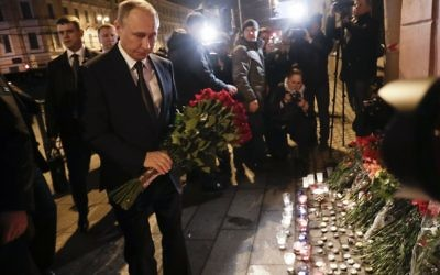 Russian President Vladimir Putin, left, lays flowers at a place near the Tekhnologichesky Institut subway station in St.Petersburg, Russi   (AP Photo/Dmitri Lovetsky)