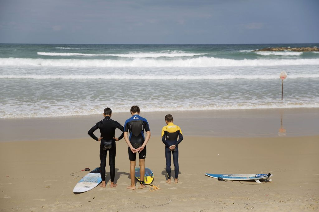 Surfers stand still as a two-minute siren sounds in memory of victims of the Holocaust.