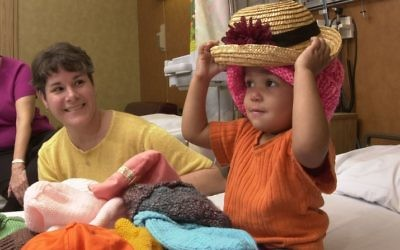 Twenty-two-month-old Naudia Turner, who had a Wilms tumor surgically removed, tried on nearly 20 hats before settling on two of her favorites. When Mad Hatters Kathy Flickinger (left) and Marion Krulas showed up, their hats offered a fun diversion to one of NaudiaÕs biweekly trips to the hospital for chemotherapy treatments.  http://www.af.mil/news/airman/0602/hatters.html (U.S. Air Force photo/Master Sgt. Lance Cheung)