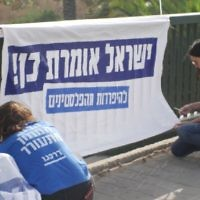 Young activists pinning up a banner for the campaign