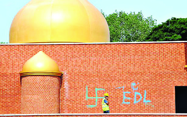 Hateful graffiti, including a swastika, daubed onto the wall o a mosque