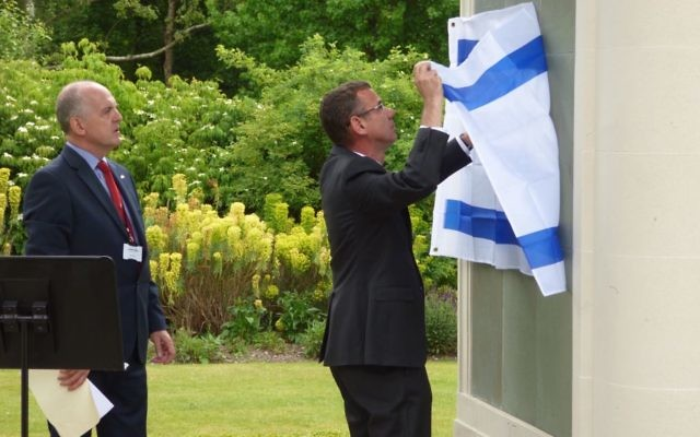 Ambassador removing Israeli flag from pillar of names of the 23 Palmach Jews who died on an operation off the Haifa/Lebanon coast in May 1941.   Credit: David Rose