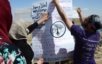 Jewish and Muslim activists putting up a poster in the Sumud camp