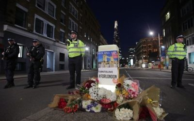 Police officers on duty next to floral tributes left on Southwark Street, London, near the scene of last night's terrorist incident.  Photo credit: Yui Mok/PA Wire