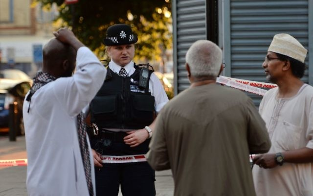 A police officer talks to local people at Finsbury Park in north London, where one man has died, eight people taken to hospital and a person arrested after a van struck pedestrians.   Photo credit: Victoria Jones/PA Wire