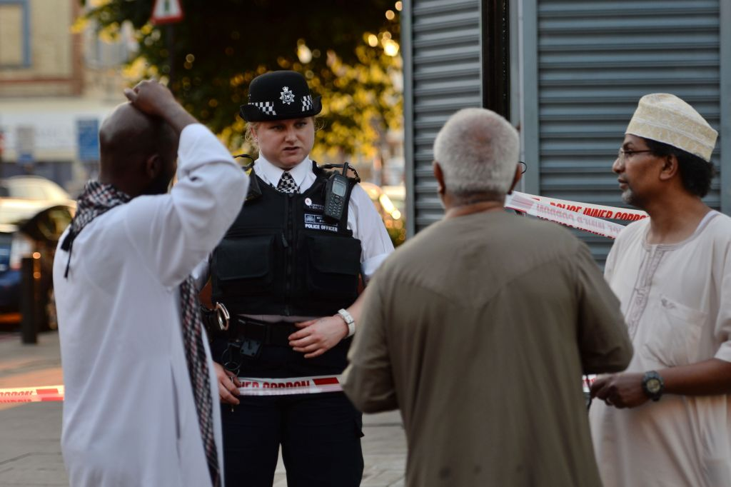 b1b2b18faf3fc6 A police officer talks to local people at Finsbury Park in north London