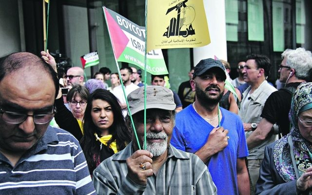 Anti-Israel demonstrators on the Al Quds Day march, holding pro-Palestine banners and flags, including that of proscribed terror group, Hezbollah.