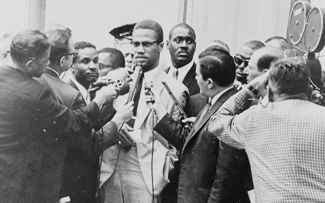 Pressman, centre right, side to the camera, in front of Malcolm X at a 1964 press conference