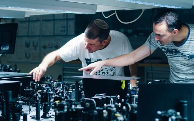 Prof. Hagai Eisenberg and graduate student Daniel Istrati study a single photon experiment at the Hebrew University's Quantum Information Science Center. (Credit: Yitz Woolf for Hebrew University)