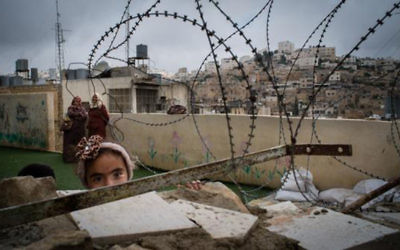 A little girl in Hebron looks out from her playground behind razor wire  Photo credit: Bath Abbey's website: http://www.bathabbey.org/whats-on/events/raising-voices-photographic-exhibition