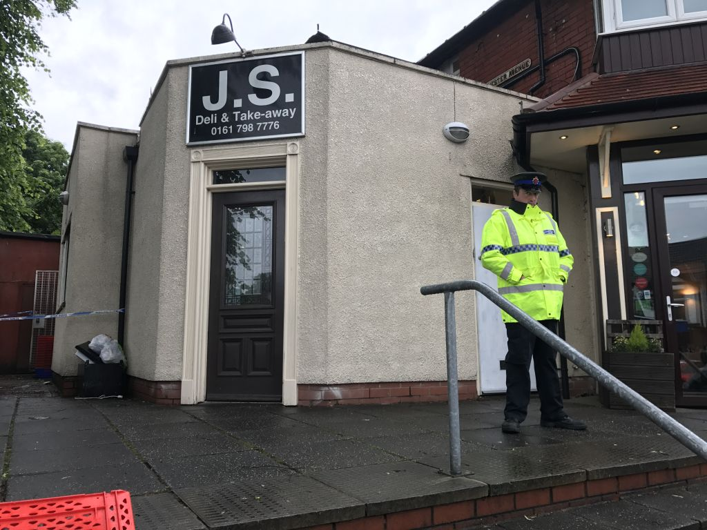 A policeman stands guard outside the JS restaurant, after the arson attack Photo credit: Steven Allen