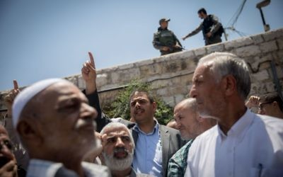 Palestinians pray as Israeli policemen guard during Friday prayers in the East Jerusalem, following a terror attack earlier that day. July 2017   Photo by: JINIPIX