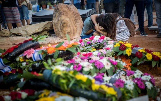 Friends and relatives mourn at the graves of Yosef Salomon (70), his daughter Haya (46) and son Elad (35), after their funeral, attended by thousands, at the Modiin Cemetery, in July, 2017.    Photo by: JINIPIX