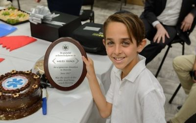 "Miles Isaacs  with a plaque which says Hatzola offer a ""grateful acknowledgment for a generous donation""."