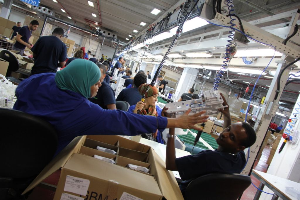 Israeli and Palestinian workers, working together at a Sodastream factory, whose headquarters are in the West Bank