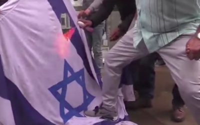 An Israeli flag being set on fire in the heart of Central London
