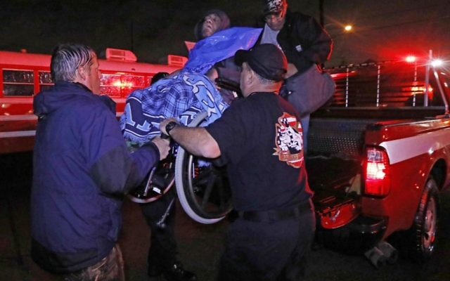 Rescue personnel help lower this wheelchair bound resident from the back of a vehicle after flooding from hurricane Harvey's almost constant rain (AP Photo/Rogelio V. Solis)