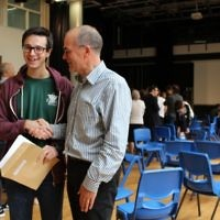 JCoSS headteacher shakes hands with a top performing student during August's A-Level results
