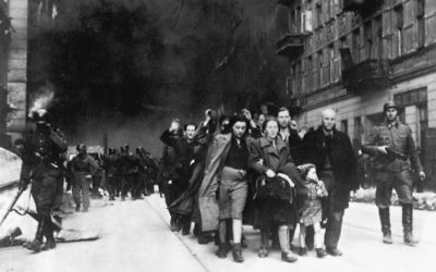 Captured Jews in the Warsaw Ghetto are led by German troops to the assembly point for deportation.