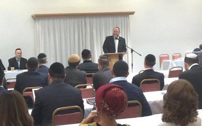 Chief Rabbi Ephraim Mirvis speaking in front of 100 Orthodox rabbis