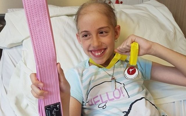 Hannah Katz with a pink karate belt in hospital, fighting but in good spirits