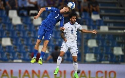 Italy's Andrea Conti heads the ball away, under pressure from Lior Raaelov