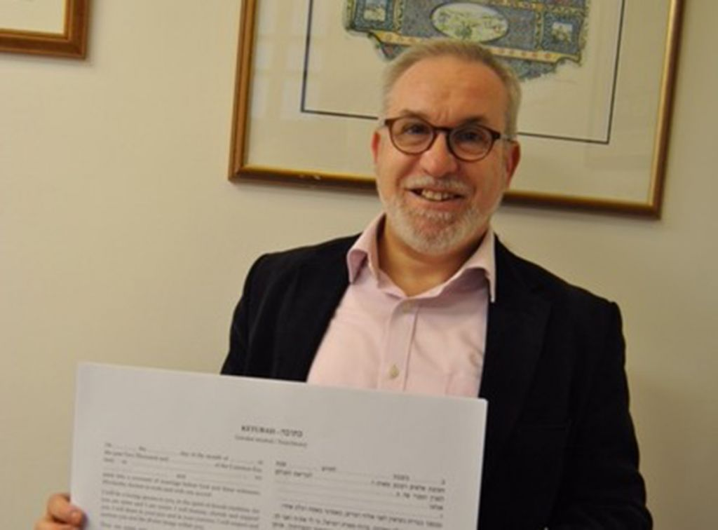 Rabbi Mark Solomon with new Ketubah text in front of classic Liberal Ketubah