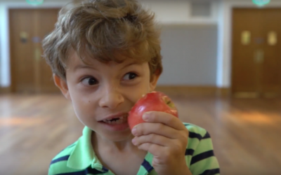 A boy bites into an apple during WLS's Rosh Hashanah video