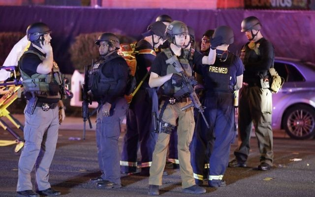 Police officers stand at the scene of the mass shooting near the Mandalay Bay resort and casino on the Las Vegas Strip,  (AP Photo/John Locher)