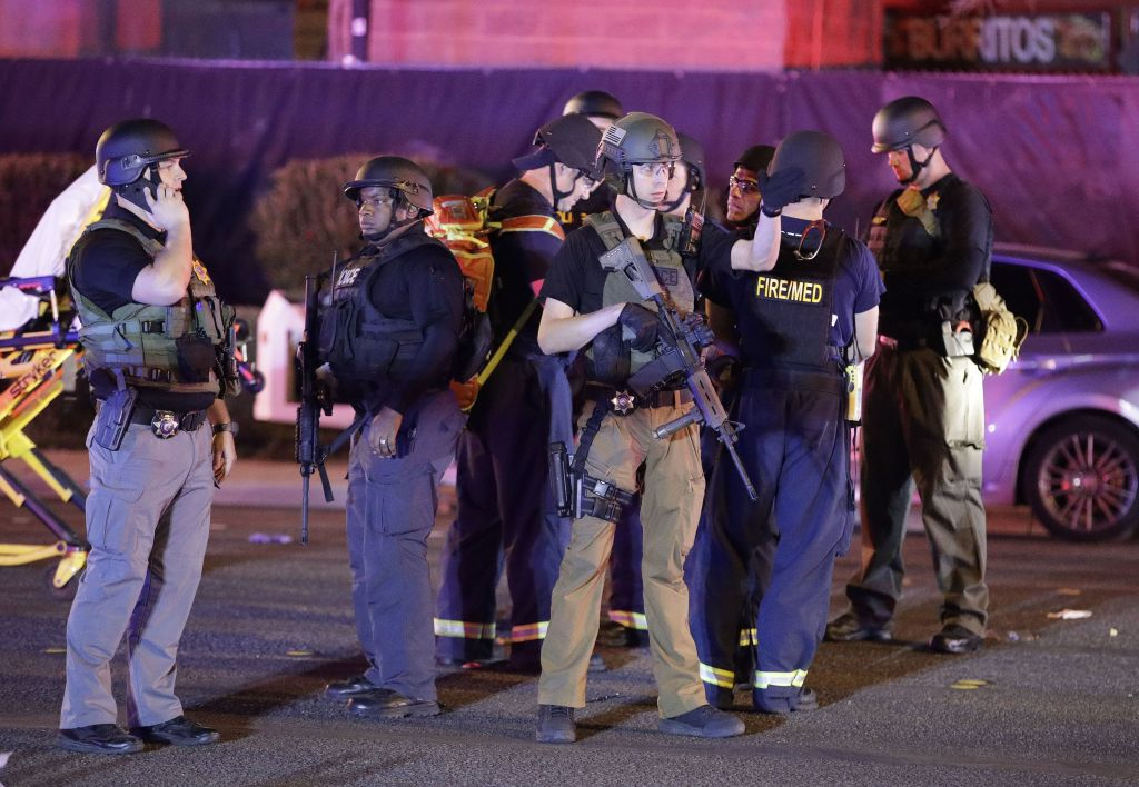 Police officers stand at the scene of the shooting near the Mandalay Bay resort and casino on the Las Vegas Strip, (AP Photo/John Locher)