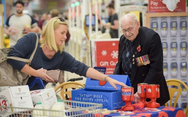 Poppy seller Ron Jones, who is 100 years old, at his selling station inside Tesco supermarket, Newport.   Photo credit: Ben Birchall/PA Wire