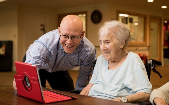 A Jewish Care resident learning how to stay connected digitally with Pawel Moczulewski, Manager of the Living Well team  Credit: Blake Ezra Photography