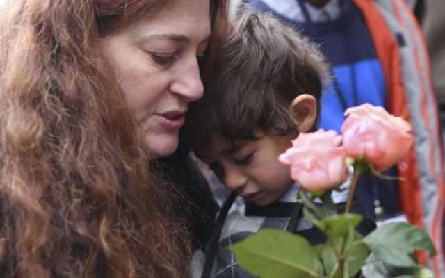 """Mandy Eisemann from Dickerson, Maryland. with her son Levi (4), relatives of the Cohn family, places flowers at four """"Stolpersteine"""" (stumbling blocks) for Karolina Cohn and her family in Frankfurt, Germany   (Arne Dedert/dpa via AP)"""