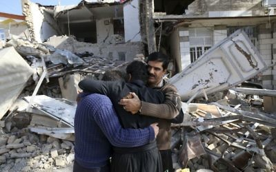 Earthquake survivors mourn in front of destroyed houses in Sarpol-e-Zahab in western Iran,  Survivors are waiting for badly needed aid, three days after a powerful earthquake along the Iraq border killed hundreds and left thousands injured.   (AP Photo/Vahid Salemi)